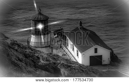 point reyes lighthouse shinning over ocean at daybreak