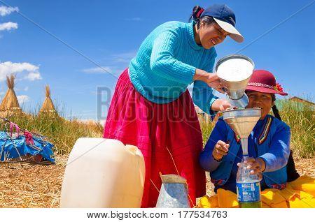 UROS FLOATING ISLANDS PERU - SEPTEMBER 19: Indigenous women sell gas on Uros Floating Islands Peru on September 19 2014