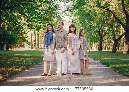 mom dad and two daughters on nature in summer park