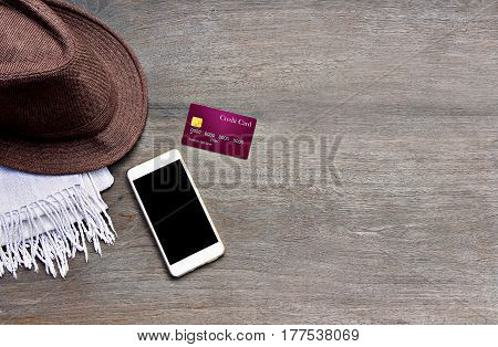 Mobile smart phone credit card and hat mad of fabric on wood texture background.