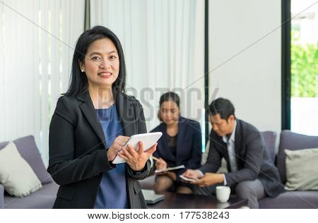 Businesswoman leader using tablet with team in corporate meeting at officeFemale leadership concept.