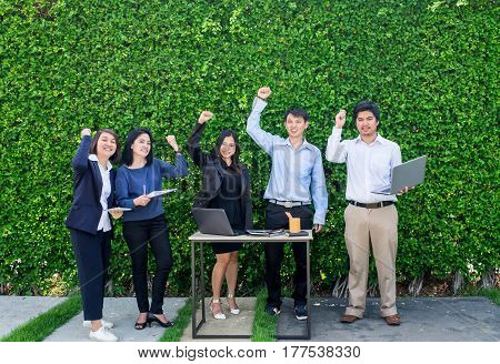 Businesswoman and businessman celebrating success of business plan at green leaf wall.