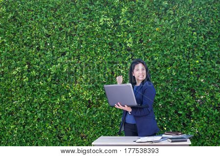 Businesswoman Arm Up To Celebrating Business Plan Success Outside Office At Green Leaf Wall