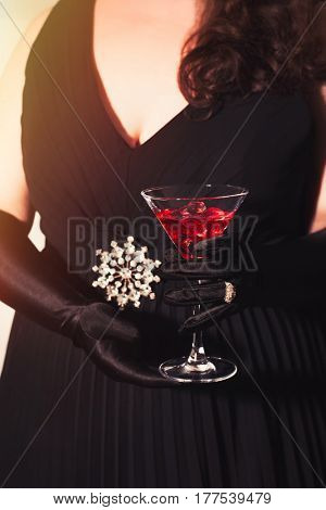 Woman wearing a black dress holding a cocktail