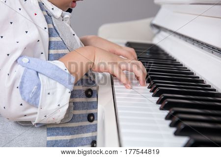 Close Up Of Asian Chinese Little Boy's Hand On Piano