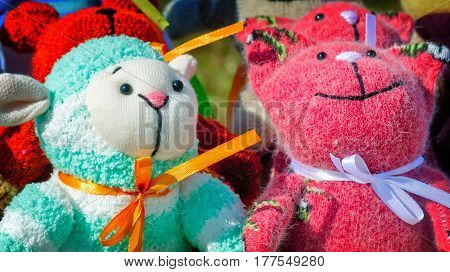 The souvenirs in the form of amusing dolls sewed from rags of fabric and laces. Are presented on a beautiful background with an embroidery.
