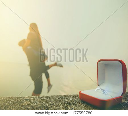wedding ring with woman and man holding on sunset at the beach