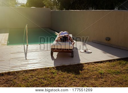 Beautiful girl is lying on a lounger by the pool and sunbathing at sunset