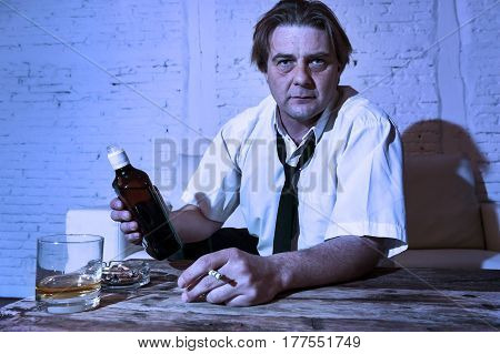 sad depressed alcoholic businessman on his 40s with loose necktie looking wasted and drunk drinking whiskey and smoking at home living room couch in alcoholism problem and alcohol addiction