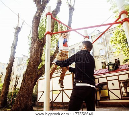 little cute blond boy hanging on playground outside, father training with fun, lifestyle children concept close up