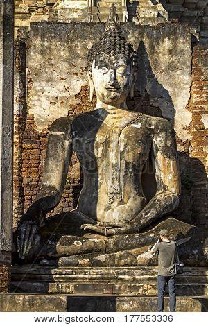 Old statue buddha at Wat Phra Si Ratanamahathat and traveler in Sisatchanalai Historical Park Sukhothai province Thailand