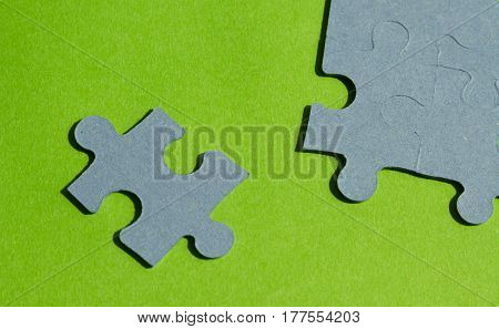 Jigsaw puzzle pieces on bright green background horizontal view with copy space