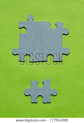 Jigsaw puzzle pieces on bright green background vertical view with copy space