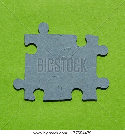 Jigsaw puzzle pieces on bright green background with copy space