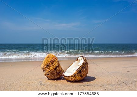 Two Halves Of Cracked Brown Coconut On White Sandy Beach With Turquoise Sea Background