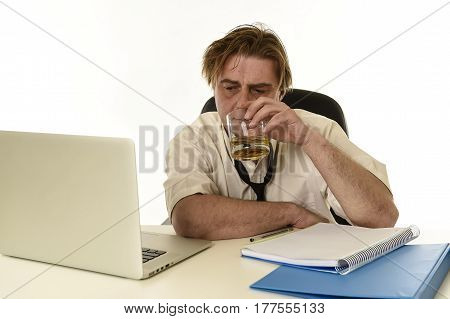 wasted and messy alcoholic businessman drinking whiskey working at laptop computer desk at office looking drunk and hangover in alcoholism problem and alcohol abuse concept