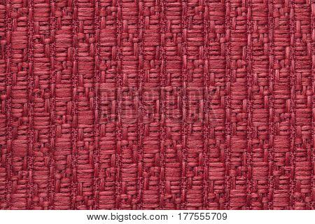 Dark red knitted woolen background with a pattern of soft fleecy cloth. Texture of garnet textile closeup.