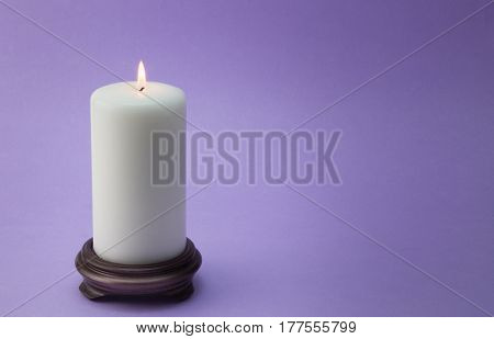 Single white lit candle on wood holder isolated on lilac / mauve background