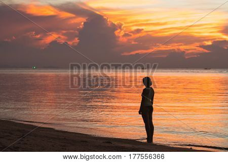 Silhouette of a girl standing on the beach admiring the sunset on the horizon.