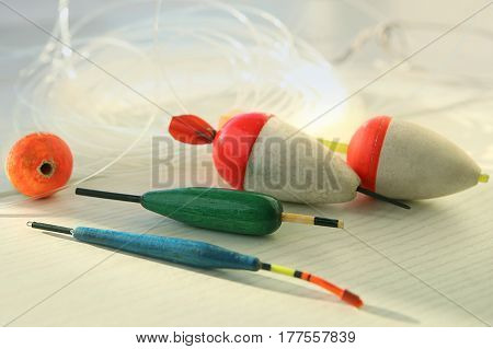 Fishing bobbers. Fishing supplies floats and line  on white wood.