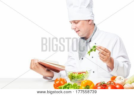 Horizontal Portrait Of The Cook At The Table With Salad And A Book Of Recipes On A White Background