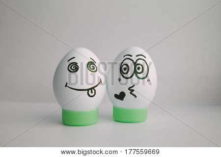Eggs are funny with a face on the stand. Concept: giving up love, kissing. Photo for your design on a white background