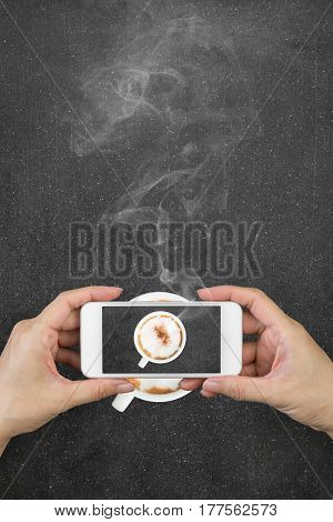 Woman hand holding and using mobilecell phonesmart phone photography and redolent cappuccino coffee on marble floor or concrete background.