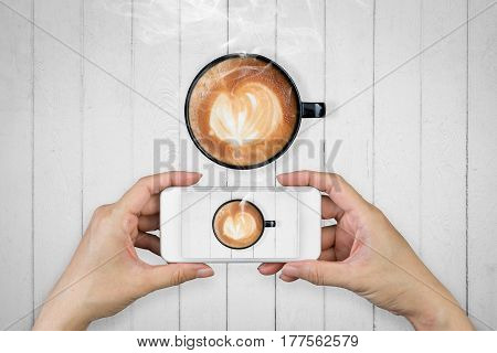Woman hand holding and using mobilecell phonesmart phone photography and redolent cappuccino coffee on wooden floor or wooden background.