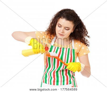 Smiling young woman holding bottle of chemistry for cleaning house. Cleaning concept. Beautiful happy girl with cleaning tools and products on white background. Housekeeper isolated portrait.