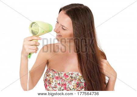 Attractive teenager girl holding hair dryer, isolated white background