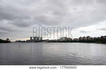 View of Neva river and microdistrict Ribatskoe on the outskirts of St. Petersburg at cloud day Russia.