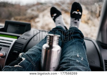 Woman Feet In Cute Socks And Jeans On Car Dashboard. Drinking Water On Road. Travel Cocept
