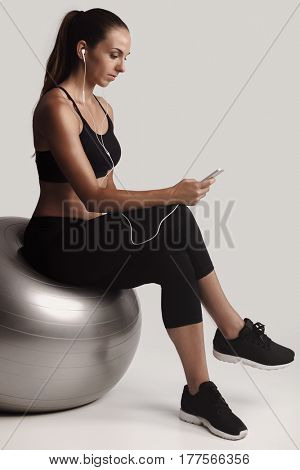 Shot of a beautiful young woman setting the music playlist for the workout.