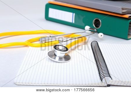 Folder file, stethoscope and note on the desk. blurred background