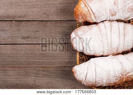 croissants sprinkled with powdered sugar on old wooden background with copy space for your text. Top view.