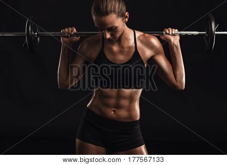 Shot of a beautiful young woman in a workout gear lifting weights