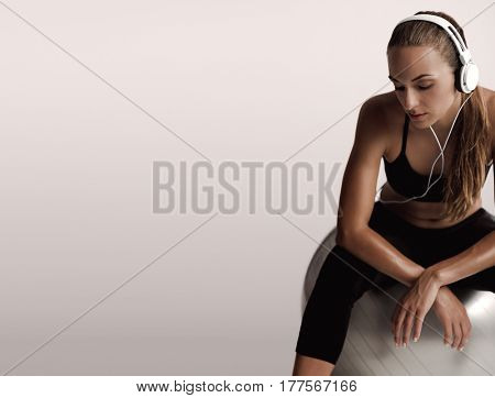 Shot of a beautiful young woman sitting on swiss ball after the train
