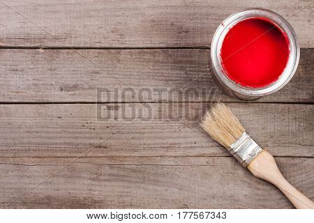 red paint in the bank to repair and paint brush on the old wooden background with copy space for your text. Top view.