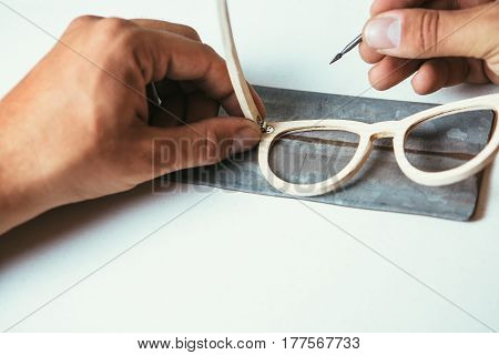 Crop faceless male hands in process of manufacturing wooden sunglasses.