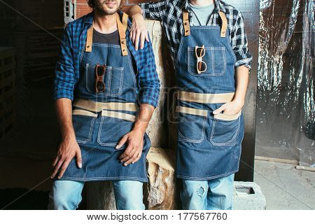 Crop faceless shot of two workers in uniform posing with sunglasses on pockets.