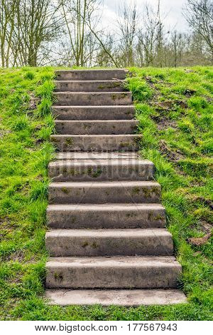 Concrete staircase in a Dutch embankment covered with green grass. It´s at the end of the winter season.