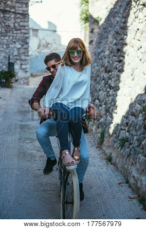 Young romantic couple in sunglasses riding bicycle together at street and laughing.