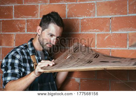 Young craftsman holding wooden planks to make sunglasses in workshop.