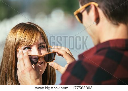 Young woman smiling to man taking off her sunglasses and looking at each other.