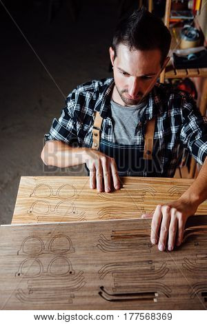 Young craftsman holding wooden planks for sunglasses production in workshop.