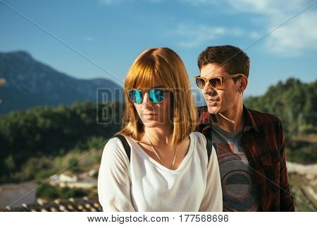 Two people wearing casual clothes and sunglasses standing on background of city and mountains and looking away.