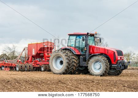 Farmer tractor working in the field. Spring time for sowing. Planting crops.