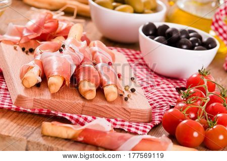 Grissini breadsticks with ham on cutting board.