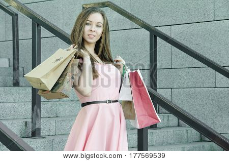 A girl in a pink dress with shopping bags and packages
