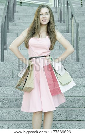 Beautiful woman with long hair in a pink dress with shopping bags on the steps